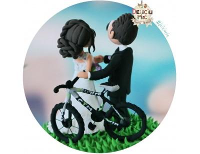 Figurine de tort pentru nunta - Mirele si Mireasa stau langa bicicleta lor