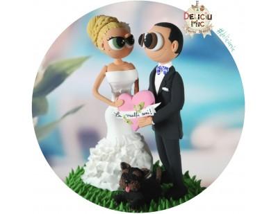 """Figurine de tort pentru nunta - Mirii tin in mana o inimioara roz pe care scrie """"La multi ani"""""""