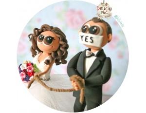 """Figurine de tort pentru nunta - Mireasa il rapeste pe Mire care are pe gura banda adeziva pe care este scris """"Yes"""""""